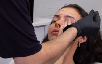 HD Brows stylist threading client's eyebrow