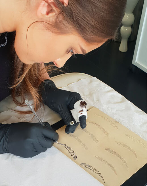 Microblading student drawing eyebrows on a practice mat