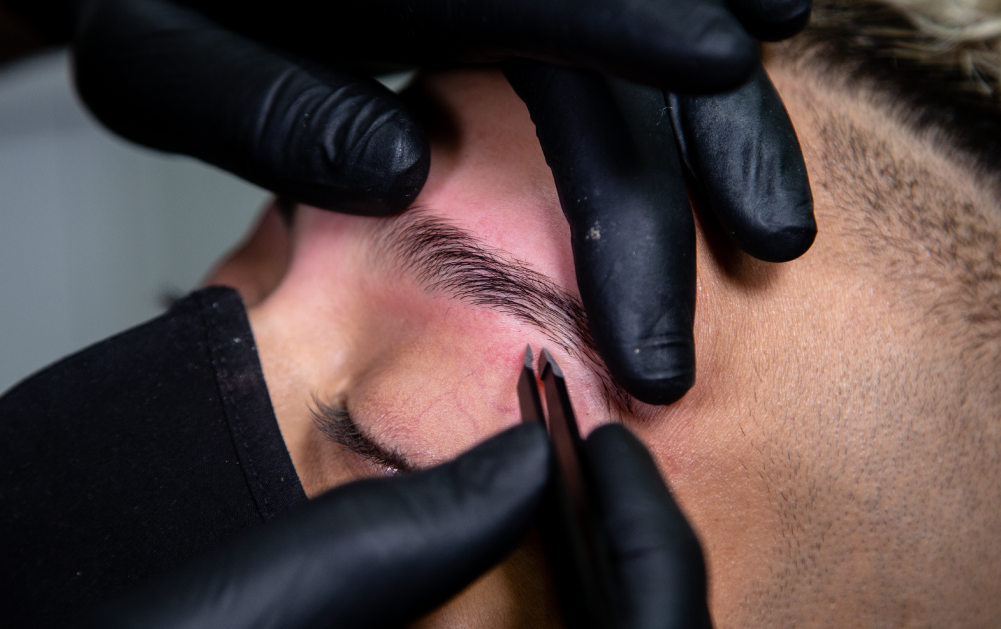 Close up of a brow stylist plucking eyebrows