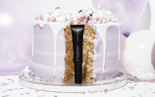 Tube of Brow Glue stood in front of a birthday cake